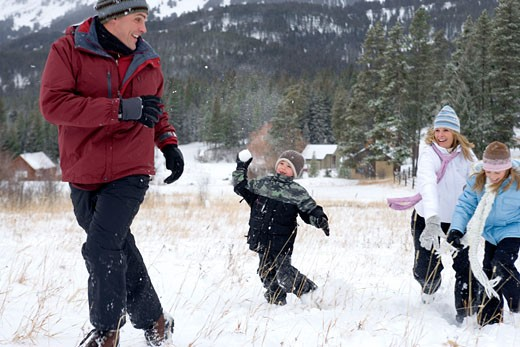 Stock Photo: 1698-151B Mature woman with her son and daughter throwing snowballs at a mature man