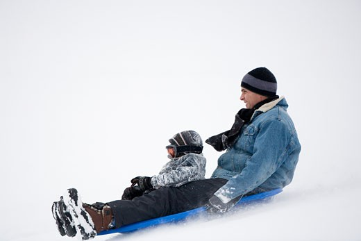 Stock Photo: 1698-174A Mature man and his son sledding