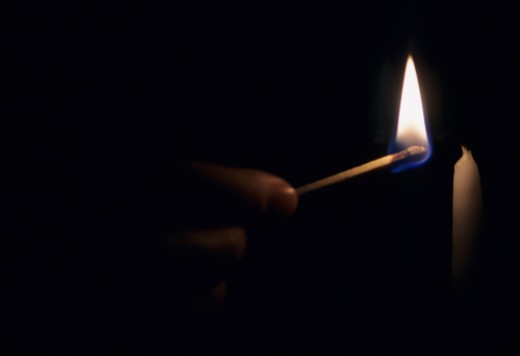 Washington, District of Columbia. A woman illuminates darkness using a match to light a candle. : Stock Photo