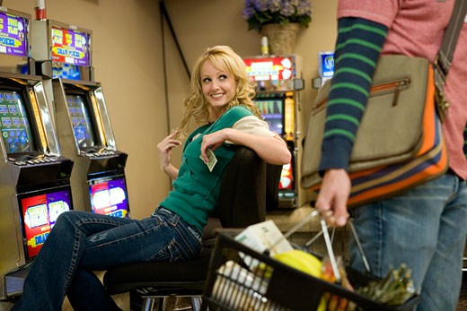 Man carrying a shopping basket with a young woman sitting behind him in a casino : Stock Photo