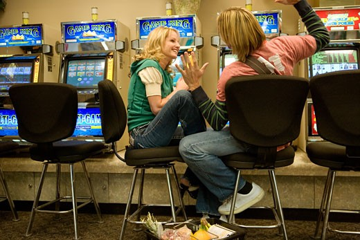 Young couple sitting in front of slot machines in a casino : Stock Photo