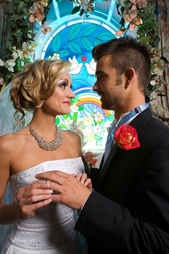 Stock Photo: 1703-115F Bride putting a ring on a groom's finger in front of a stained glass window
