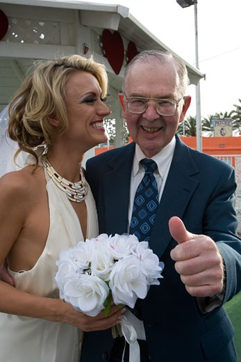 Stock Photo: 1703-121C Bride smiling with a senior man giving a thumb's up