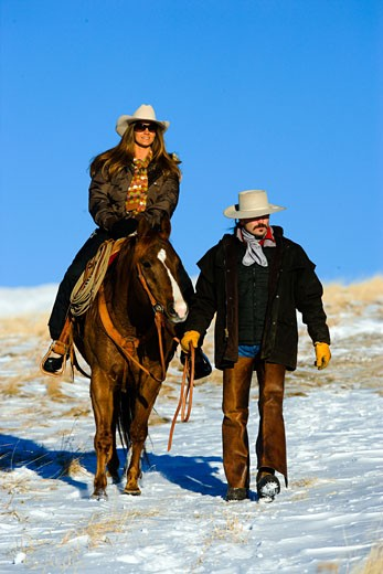 Stock Photo: 1707-127A Mid adult woman riding a horse with a mid adult man guiding them