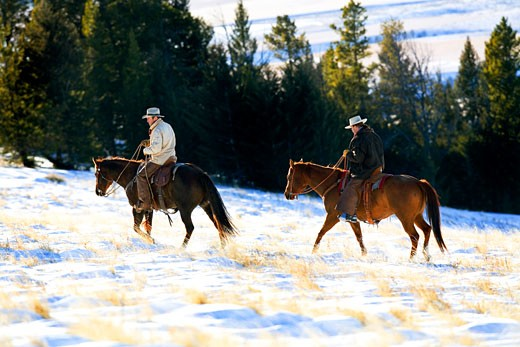 Stock Photo: 1707-132B Two men riding horses in a snow covered field