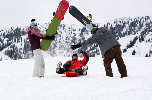 Mid adult man sledding between a mid adult woman and a mid adult man : Stock Photo