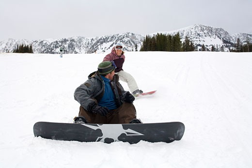 Mid adult man sitting on snow with a mid adult woman sliding behind him : Stock Photo