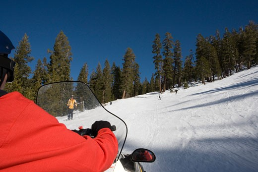 Three people skiing downhill with another person riding a snowmobile : Stock Photo
