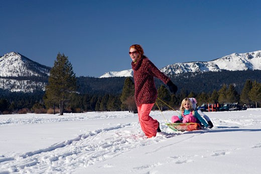 Stock Photo: 1712-123D Mature woman pulling her daughters on a sled