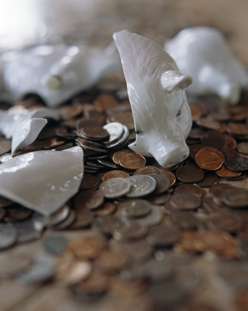 Close-up of a broken piggy bank with coins : Stock Photo