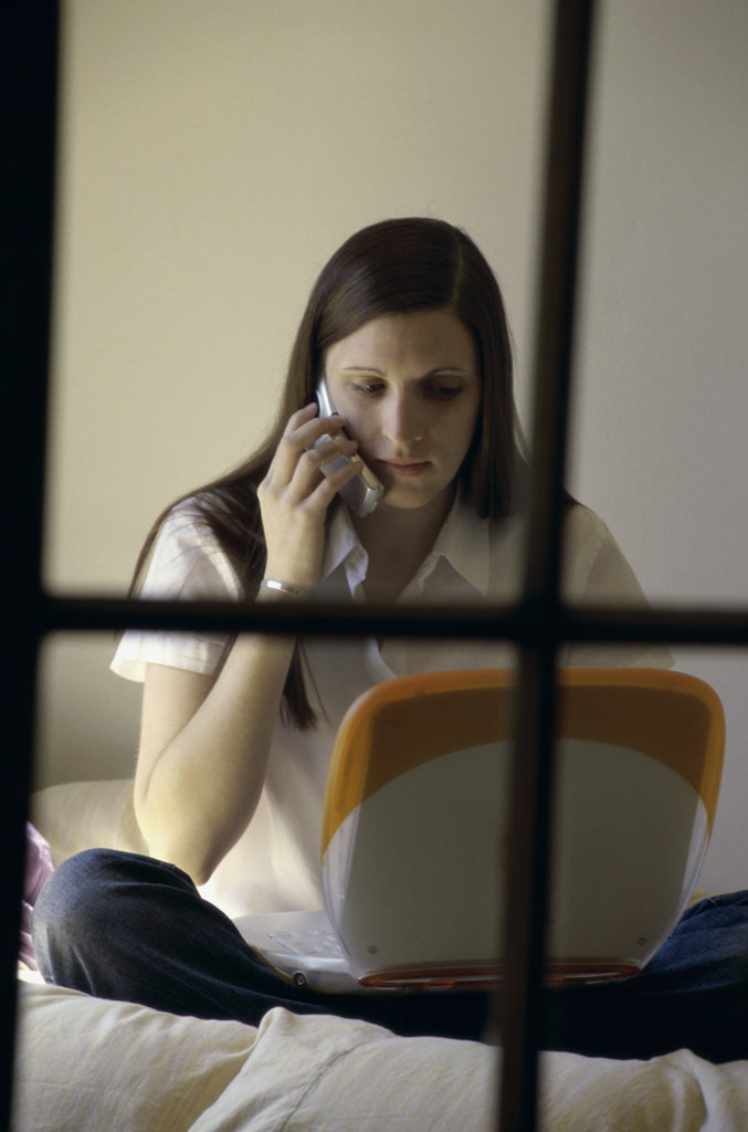 Teenage girl sitting on a bed in front of a laptop talking on a mobile phone : Stock Photo
