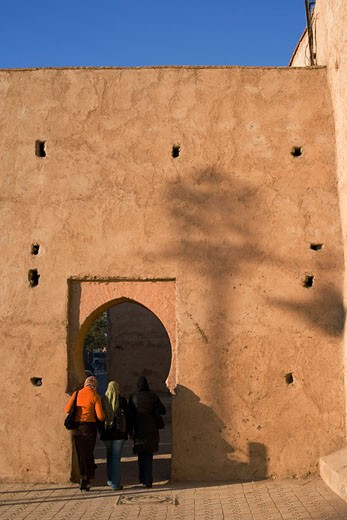Tourists entering under an archway in a fortified wall, Marrakesh, Morocco : Stock Photo