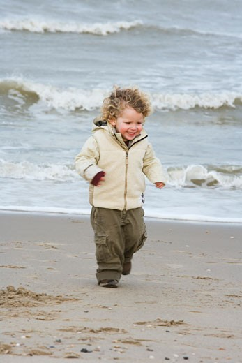 Boy walking on the beach : Stock Photo