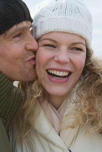 Stock Photo: 1727-116L Mid adult man kissing a mid adult woman