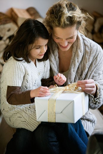 Mid adult woman and her daughter opening a Christmas present : Stock Photo