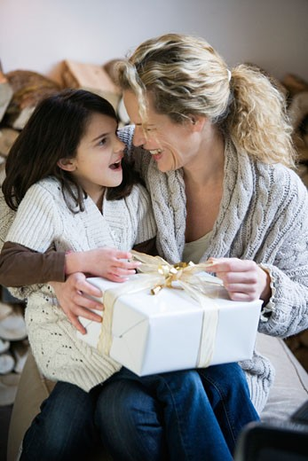 Stock Photo: 1727-124E Mid adult woman and her daughter opening a Christmas present