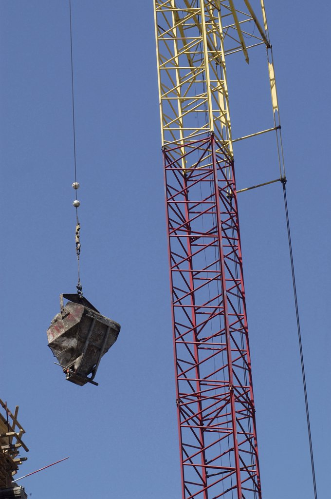 Stock Photo: 1729-131 Low angle view of a crane hoisting a cement mixer