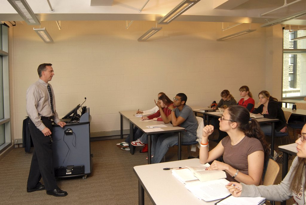 College students listening to the professor in a classroom : Stock Photo