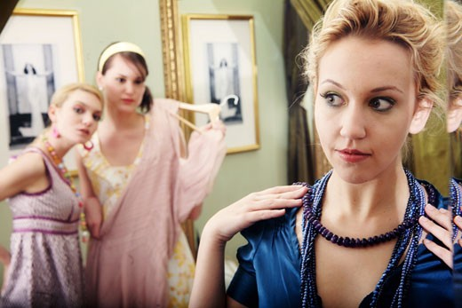 Stock Photo: 1730-105 Close-up of a young woman a necklace with her two friends watching in the background