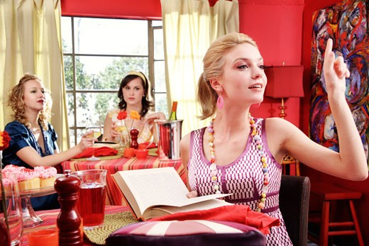 Stock Photo: 1730-112F Young woman holding a book with two young women dining in a resturant behind her