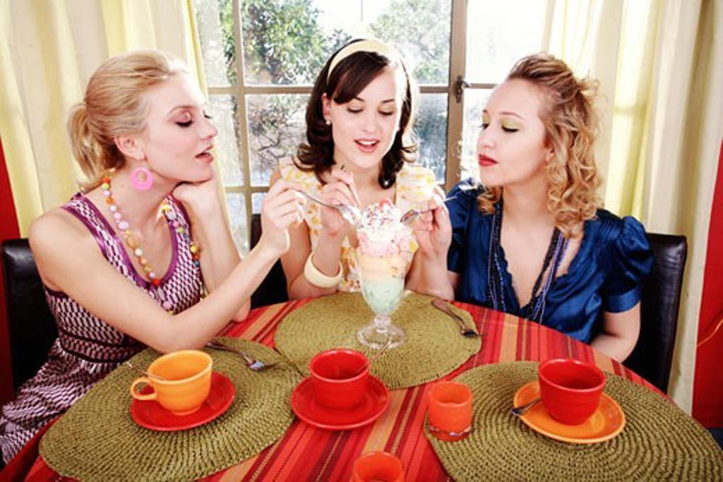 Three young women eating ice cream : Stock Photo