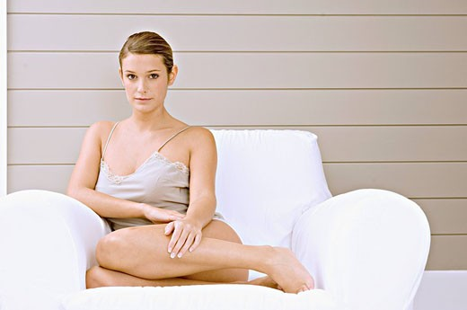 Portrait of a young woman sitting in an armchair : Stock Photo