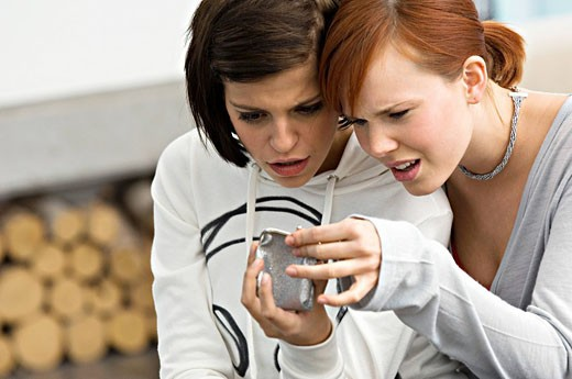 Stock Photo: 1738R-10541 Two young women looking into a change purse