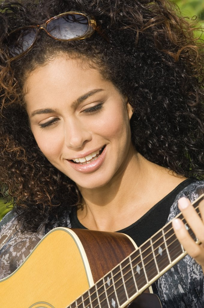 Woman playing a guitar and smiling : Stock Photo
