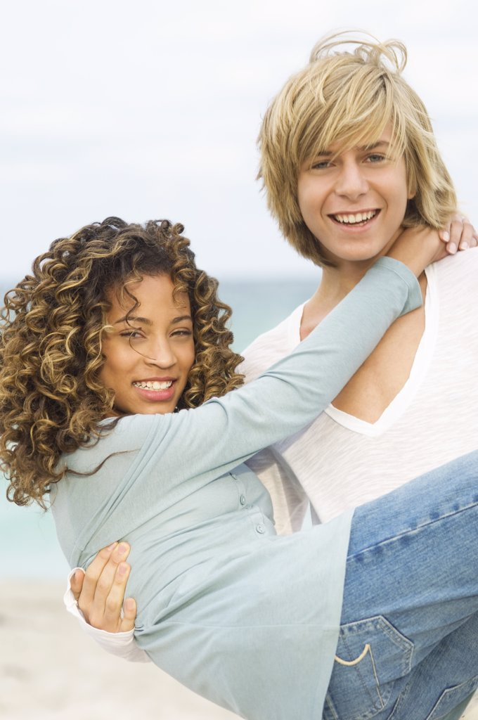 Teenage boy carrying a girl on the beach : Stock Photo