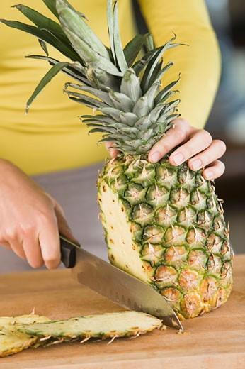 Stock Photo: 1738R-11837 Woman cutting a pineapple