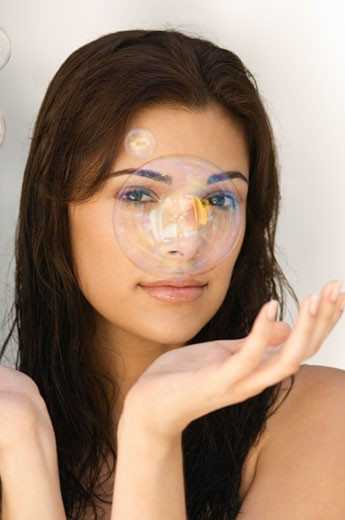 Soap bubble in front of a woman's face : Stock Photo