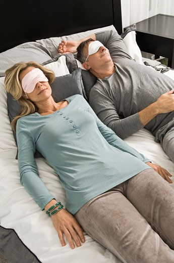 Couple sleeping in bed wearing eye masks : Stock Photo
