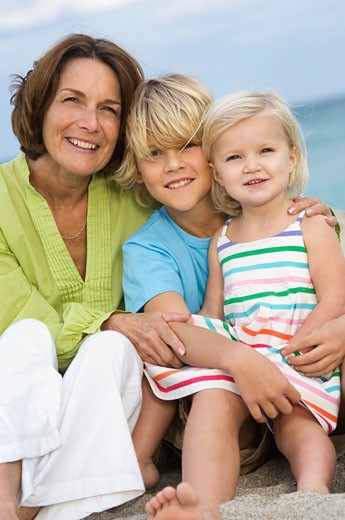 Woman sitting with her grandchildren on the beach : Stock Photo