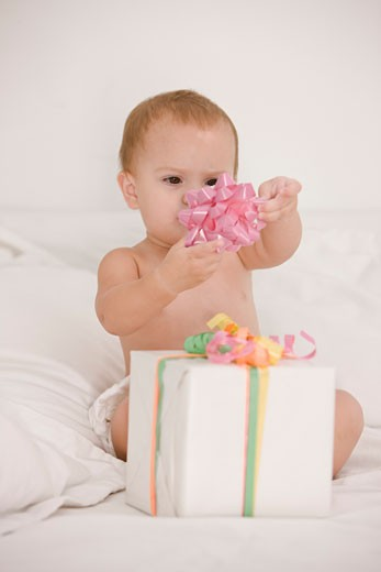 Baby girl playing with a bow on the bed : Stock Photo