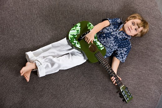 Boy lying on a round table and playing a guitar : Stock Photo
