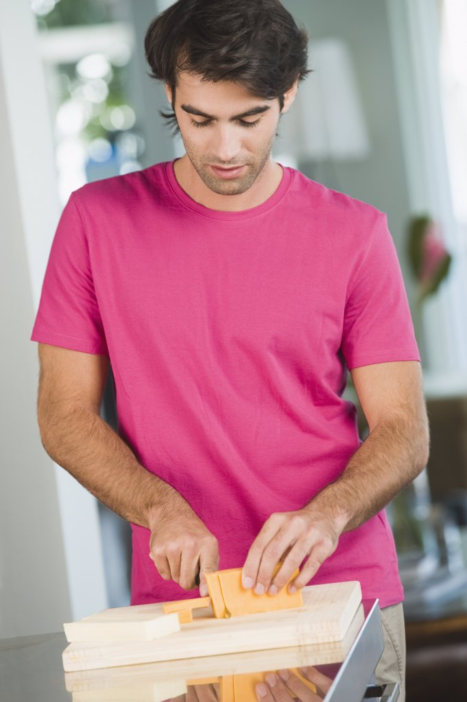 Stock Photo: 1738R-12652 Man cutting cheese slices