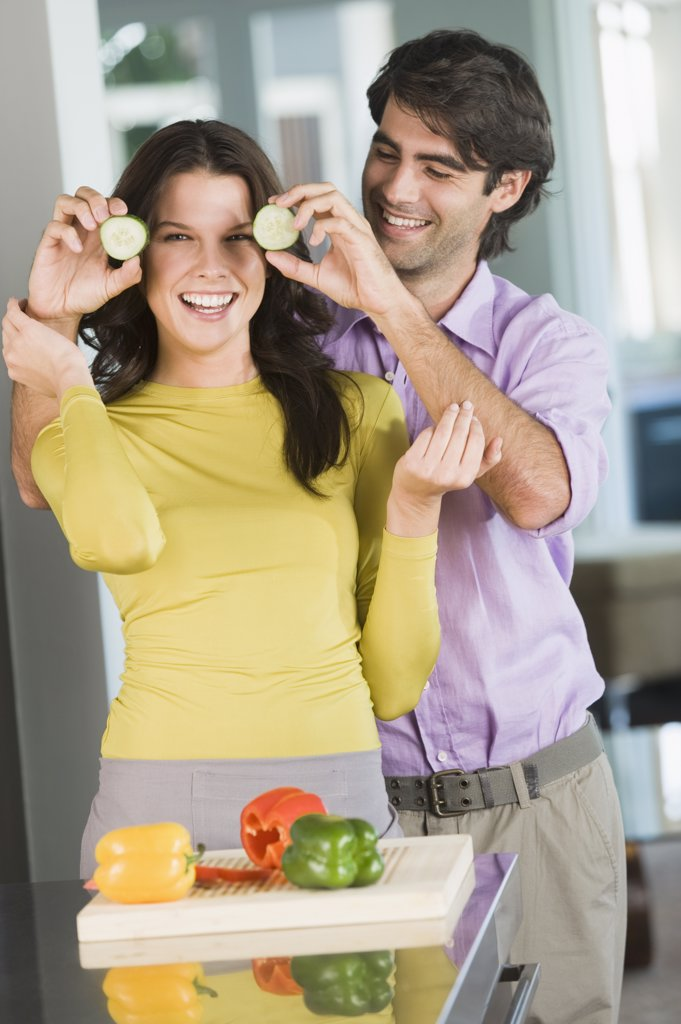 Man holding cucumber slices in front of a woman in the kitchen : Stock Photo