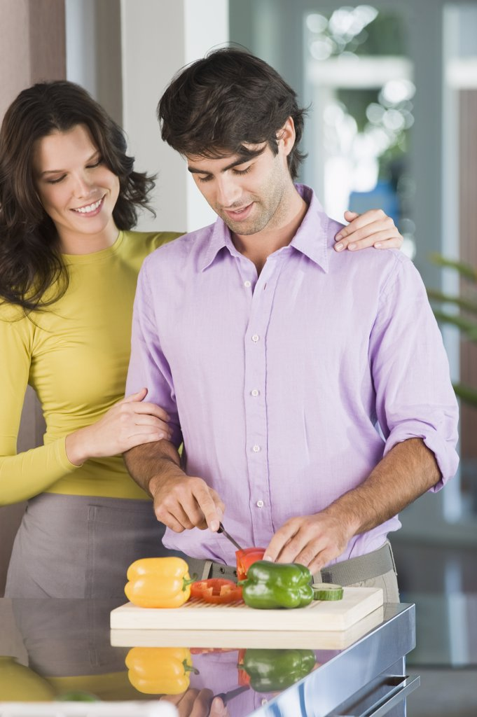 Stock Photo: 1738R-12691 Man cutting bell peppers with a woman standing beside him