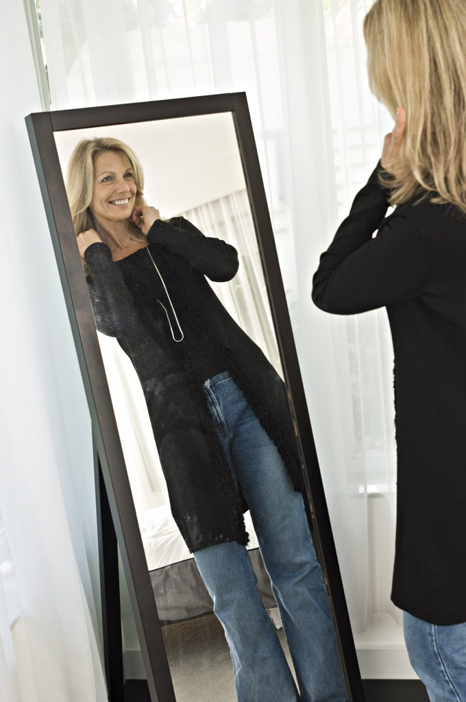 Woman trying on a dress in front of a mirror : Stock Photo