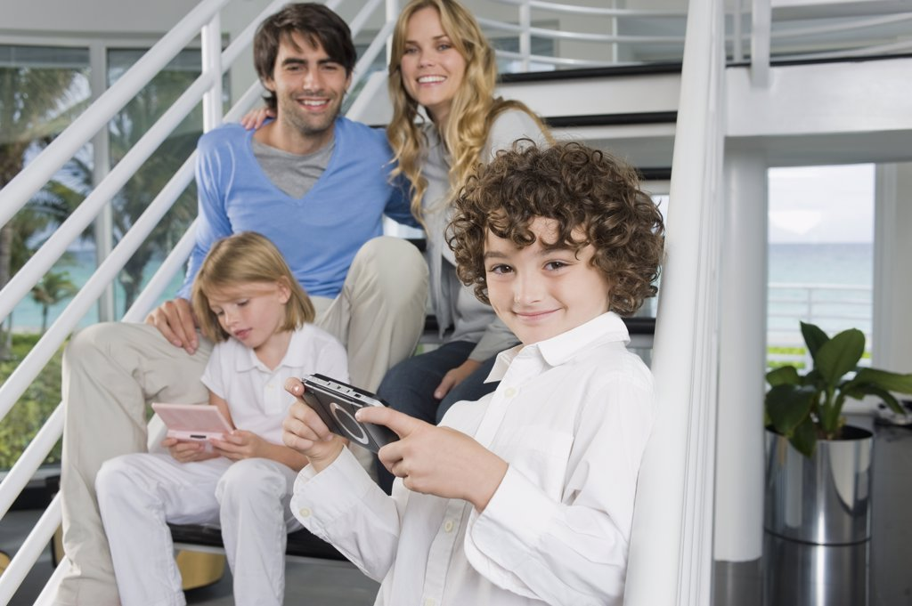 Parents sitting on steps with their children playing video games : Stock Photo