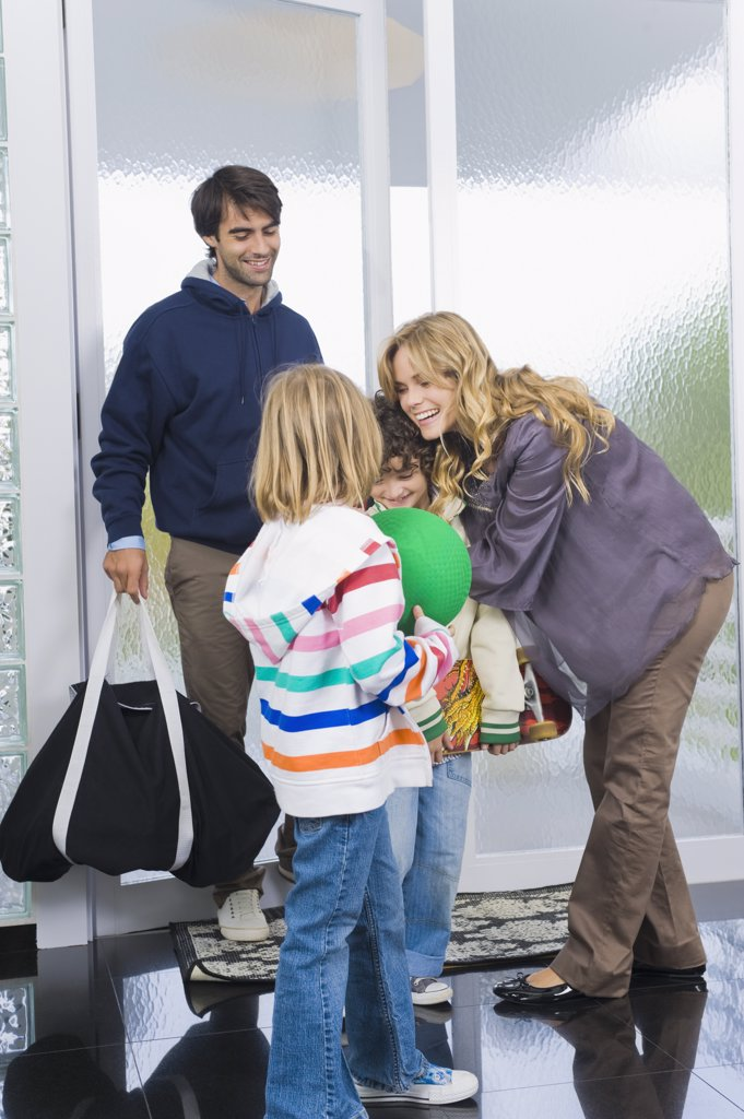 Stock Photo: 1738R-12815 Woman greeting her children and husband at the door of a house