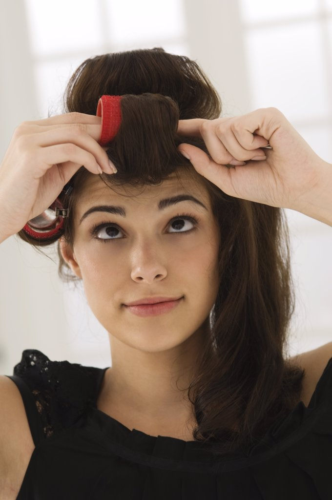 Stock Photo: 1738R-12948 Close-up of a woman removing hair curlers