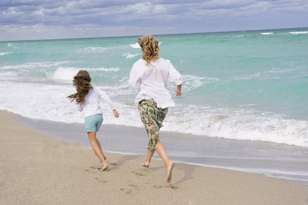 Woman running with her daughter on the beach : Stock Photo
