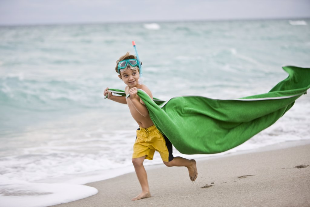 Stock Photo: 1738R-13471 Boy wearing a scuba mask and running on the beach