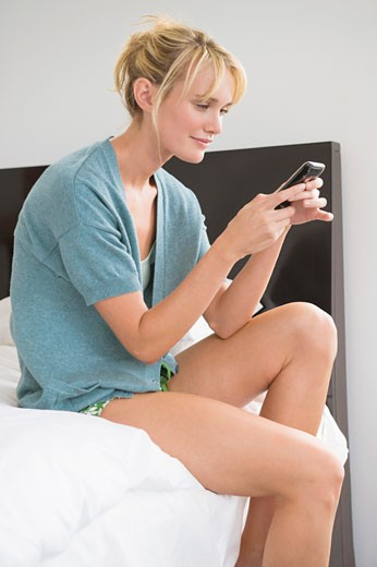 Woman text messaging on a mobile phone : Stock Photo
