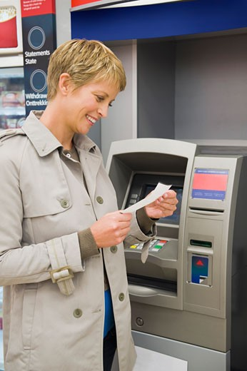 Stock Photo: 1738R-14415 Woman reading a transaction slip at an ATM and smiling