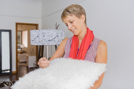 Stock Photo: 1738R-14581 Woman holding a rug in a store