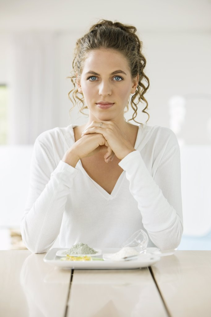 Stock Photo: 1738R-15342 Portrait of a woman sitting at a table with clays on a plate