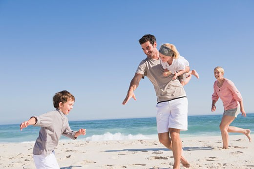 Family enjoying vacations on the beach : Stock Photo
