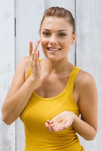 Woman applying moisturizer on her face : Stock Photo